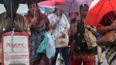 Shoppers carry non-plastic bags during rains at a market in Mumbai on Saturday.