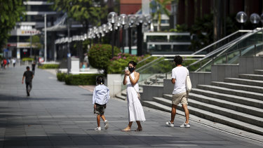 People wearing protective face masks walk along the Orchard Road shopping belt in Singapore.