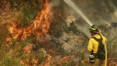 A firefighter puts out a hotspot north-west of Forrest Falls in California as the El Dorado Fire continues to burn.