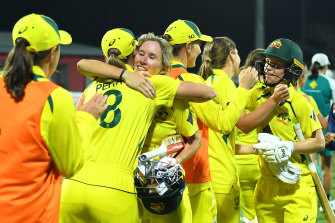 Beth Mooney and Nicola Carey celebrate with teammates after their victory.
