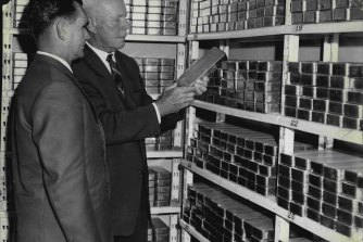 Mr. M.A. Aitken (left), internal audit officer, and Mr. T.W. Chaplin, chief cashier, handling a bar of gold worth £6,250 in the vaults of the Reserve Bank in 1964.