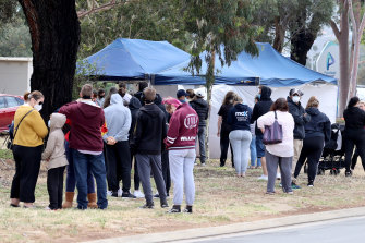 Queues of people line up for a COVID-19 test in Adelaide on Monday.