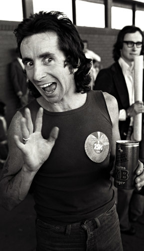 Bon Scott waves to the cameras in 1976 after an overseas tour.