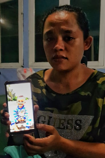 Nikita, stranded at the airport in Makassar, Sulawesi,  holds a photo of Zidan her two-year-old son, who has been missing since the earthquake.