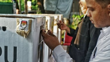 Party observers check a sealed ballot box before the start of voting at a South Jakarta polling station on Wednesday.
