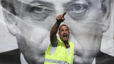 A man chants slogans next to a banner showing Israeli Prime Minister Benjamin Netanyahu during a protest against the rising cost of living, in Tel Aviv recently.