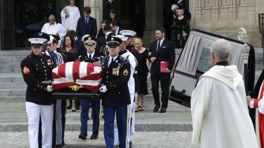 The coffin of Senator John McCain, followed by family members, is carried out of Washington National Cathedral in Washington, on Saturday.