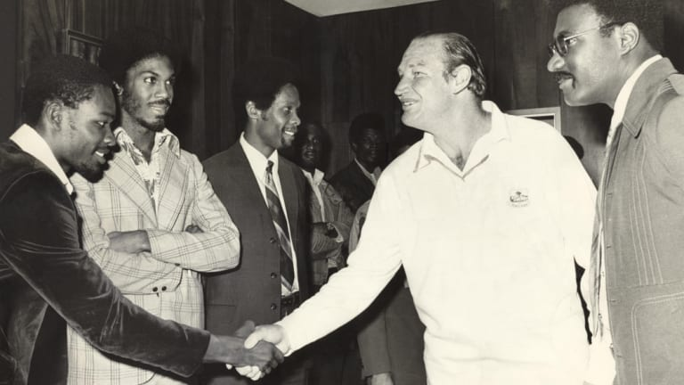 Kerry Packer meets the West Indies cricket team, among them Clive Lloyd to his left and opposite him with his arms folded, Michael Holding, as World Series Cricket gets going in 1977.