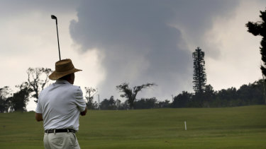 A golfer watches an ash plume rise from the summit of Kilauea volcano on Wednesday.