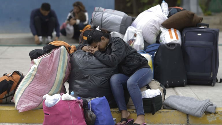 Carolina Torres, a Venezuelan woman who worked as a life insurance saleswoman in her home country, rests on her luggage in the border town of Tumbes, Peru.