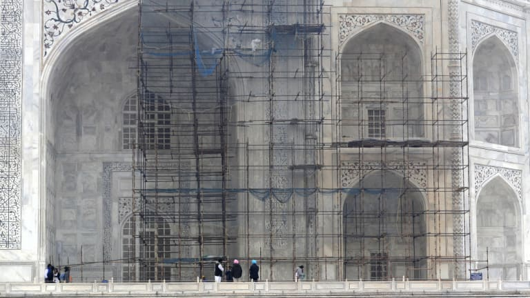 Tourists walk past a discoloured wall of the Taj Mahal caused by environmental pollution which stands out in contrast against one which has been cleaned.