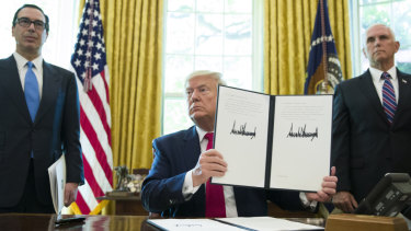 President Donald Trump holds up a signed executive order to increase sanctions on Iran.