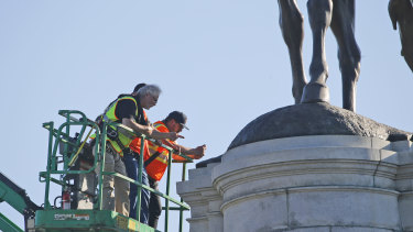 A crew from the Virginia Department of General Services inspects the base of the statue of Confederate General Robert E. Lee on Monument Avenue on Monday.