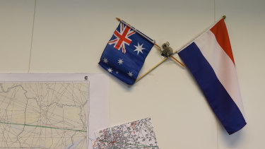 An Australian and Dutch flag hang on the wall next to maps showing the flight path of MH17 in the National Police of the Netherlands criminal investigation building in 2015.