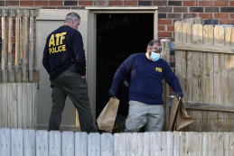 Investigators remove items from the basement of a home Saturday