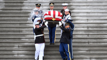 The casket of John McCain is being carried down the steps of the US Capitol last year.