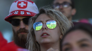 Reflected glory: A Swiss fan watches on as Switzerland and Serbia battle in a Group E qualifier.