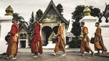 Buddhist monks line up to collect alms in Luang Prabang.