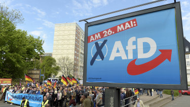 AfD supporters walking near a party elections poster in Erfurt, Germany.