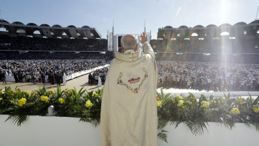A priest waves to the crowd at Sheikh Zayed Stadium in Abu Dhabi during the UAE's first-ever papal Mass in February.