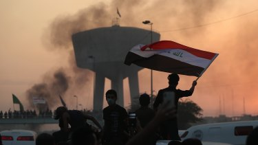 Anti-government protesters wave flags during a demonstration in Baghdad, Iraq.