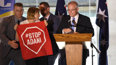 A Stop Adani protester takes to the stage where Australian Prime Minister Scott Morrison was making a speech at a the Valley Chamber of Commerce business luncheon in Brisbane on Monday.