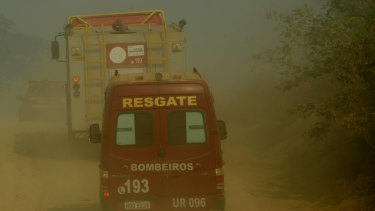Firefighters advance through smoke near the National Forest of Jacunda in Rondonia state, part of Brazil's Amazon.