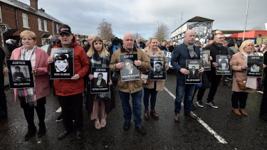 Paul Doherty (centre, holding a picture of Bernard McGuigan, with his niece, Caitlin, to his right) on a protest march for justice for Bloody Sunday victims.