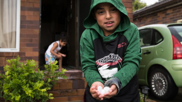 Fadi and Leya Amine collect hail stones in their front yard in Maroubra.