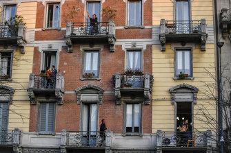 People in lockdown stand on their balconies in Milan, Italy.