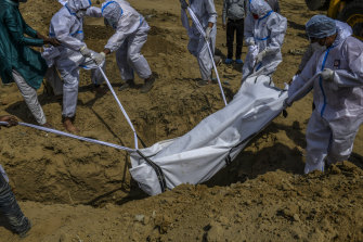 A coronavirus victim's body is buried at a cemetery in New Delhi.