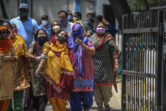 Distraught women outside a hospital where coronavirus cases and deaths are increasing, in New Delhi.