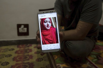 Shahid Nazir Bhat, a Muslim, displays a photograph of Manmeet Kour Bali, a Sikh by birth who converted to Islam to marry him, in Srinagar, India.
