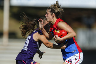 Lauren Pearce, right, of the Demons, fends off a tackle in a Fremantle Dockers clash in March.