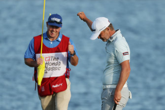 Matt Jones celebrates with caddie Lance Bailey on the 18th green after his victory at the Honda Classic.