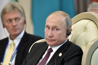 Russian President Vladimir Putin, front, and his spokesman Dmitry Peskov.