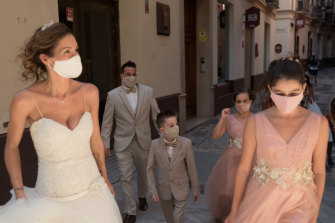 Masked newlyweds and their wedding party in Malaga, Spain.