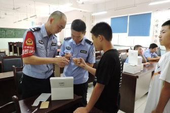 Police officers from the Jiufeng police station in Shaanxi Province collect DNA samples from a boy.