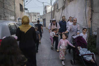 Israeli settlers walk past a Palestinian family in the Silwan district of East Jerusalem. Efforts to force Palestinians from Sheikh Jarrah set the stage for the recent Gaza war, and a similar dynamic looms here.