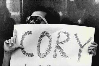 A Filipino protester carries a sign supporting Corazon Aquino.