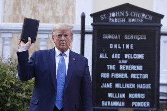 """US President Donald Trump poses with a Bible outside St John's Episcopal Church near the White House in June. A new super PAC says Trump has """"in a predatory way attached himself to Christians""""."""