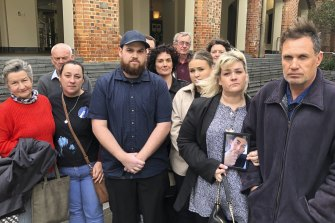 Pamella and Chris Fink, far right, were surrounded by family and supporters during the Supreme Court hearing where they sought to get an inquest into their son's suicide.