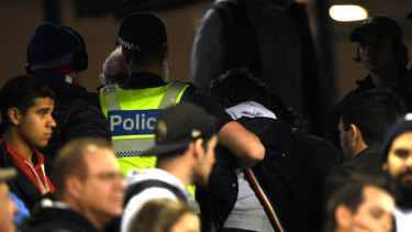 Police remove a member of the crowd at Marvel Stadium.