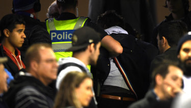 Police remove a member of the audience after the Round 13 AFL match between the Carlton Blues and the Western Bulldogs at Marvel Stadium in Melbourne, Saturday, June 15, 2019