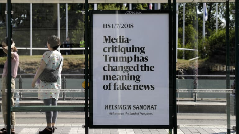 A poster reading 'Media-critiquing Trump has changed the meaning of fake news' is displayed by Finnish newspaper Helsingin Sanomat at a stop for public transport in Helsinki, in July.