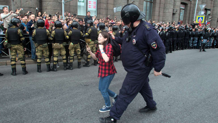 A Russian police officer detains a teenager during rally protesting retirement age hikes in St Petersburg, Russia.