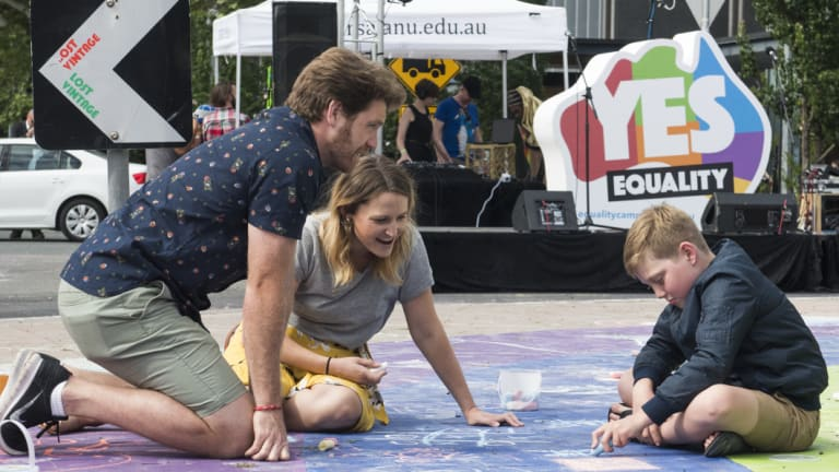 Daniel Little, Natalie Plummer, and Logan Little, 9, of Curtin take part in drawing with chalk on the rainbow roundabout.