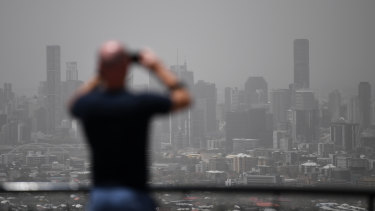A visitor to the Mt Coottha lookout takes a photo of smoke haze as a result of bushfires blanketing central Brisbane, Saturday, November 9, 2019. High temperatures and strong winds are creating extreme fire condition for parts of south east Queensland.