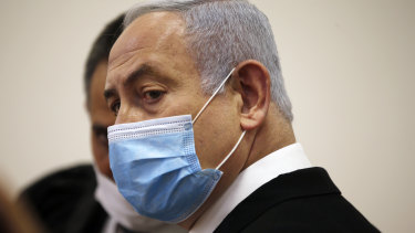 Israeli Prime Minister Benjamin Netanyahu, wearing a face mask in line with public health restrictions due to the coronavirus pandemic, stands inside the court room as his corruption trial opens at the Jerusalem District Court, Sunday, May 24, 2020.