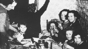 A woman slices bread for the eight children crowded around a table at meal-time.